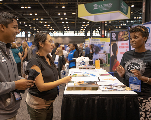 A representative of Encounter Bible Series discusses the organization's resources with two attendees of the 2018 NAD Teachers' Convention.