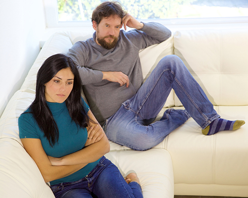 married couple sitting on sofa after argument