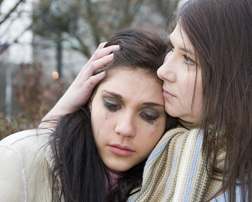 mother comforts crying teen daughter