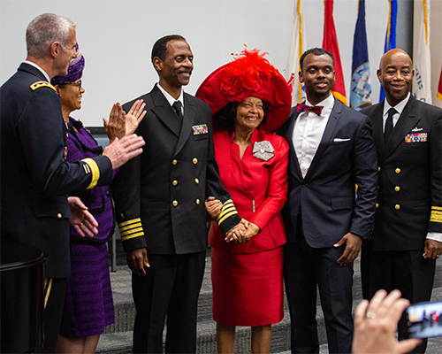 Washington Johnson, II poses with family and colleagues after receiving his new service dress coat, which reflects his new ranking.