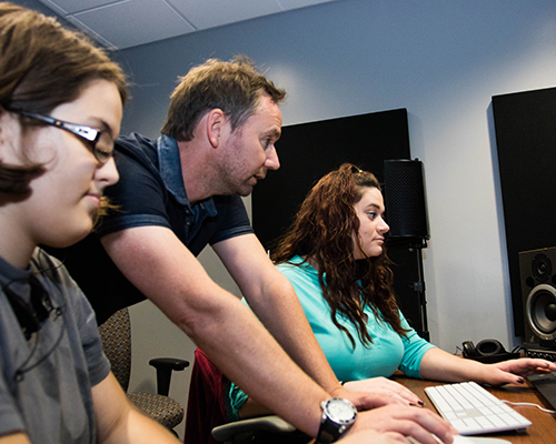 Kyle Portbury and two students edit films at Southwestern Adventist University