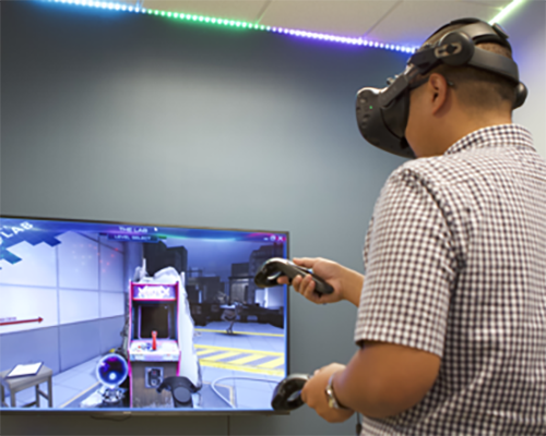 Religious studies major Gregory Jhanapin tries out a virtual reality video game in La Sierra University's new virtual reality and artificial intelligence lab.