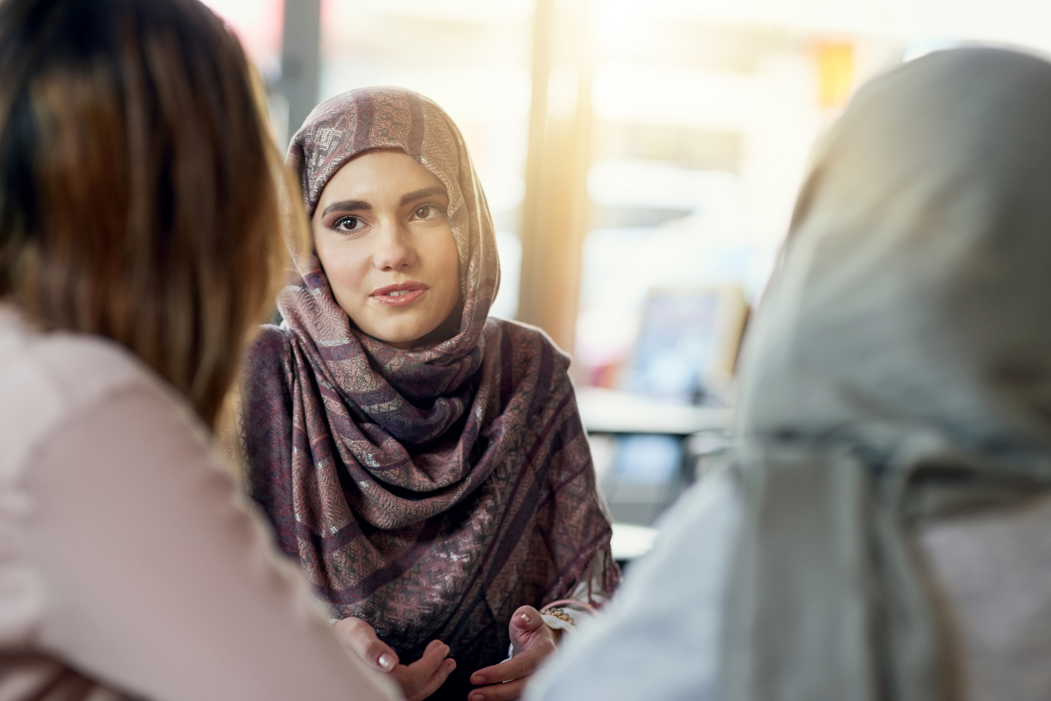 stock photo of two Muslim women talking to third women
