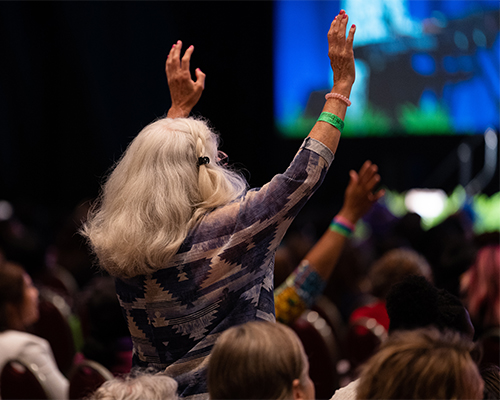Convention attendee stands and lifts her hands in response to praise and worship.
