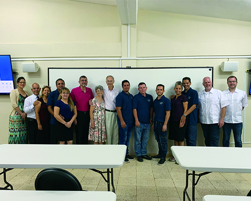 Personnel from Southern Adventist University and the Cuba Adventist Theological Seminary pose for a photo in the former storage room turned into a virtual classroom.