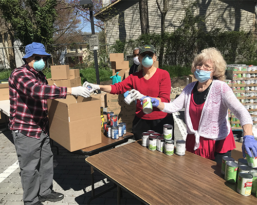 Volunteers of Adventist Community Services Greater Washington sort cans while wearing gloves and masks.