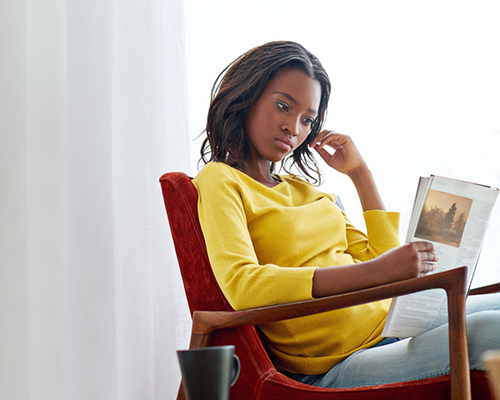 African American woman reading magazine stock photo
