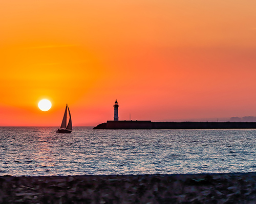 sailboat, sunset, and lighthouse stock photo