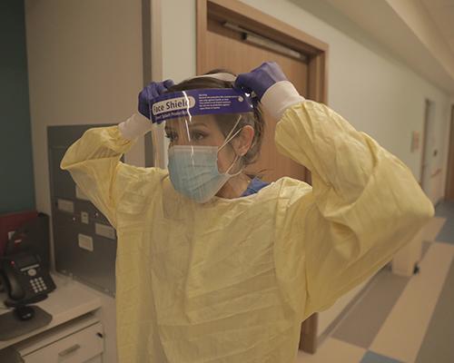 Wamack putting on PPE