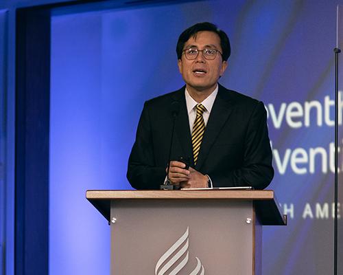 Kyoshin Ahn delivers secretary's report.
