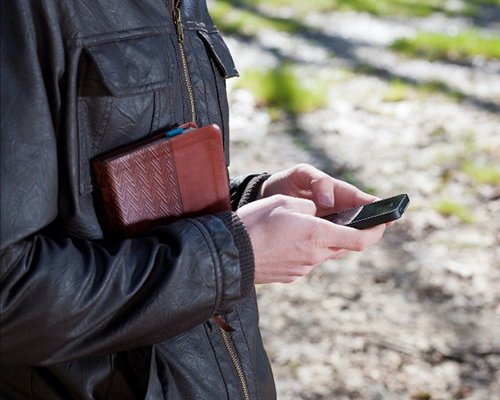 Man holding bible and cell phone