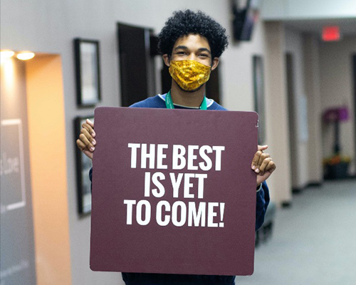 "Man holding sign ""The Best is Yet to Come!"""