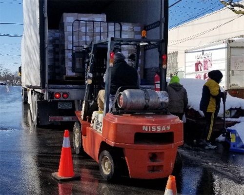 Forklift with truck filled with packages