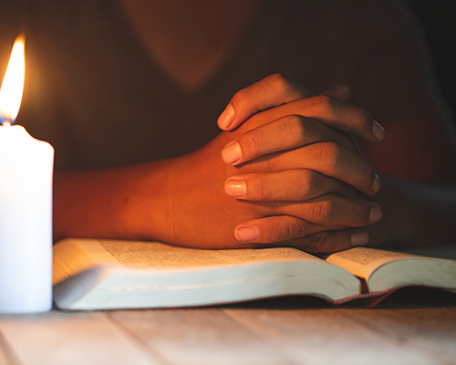 stock photo of praying person with Bible in candlelight
