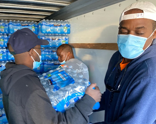 Oakwood University Church and Breath of Life workers carry cases of water