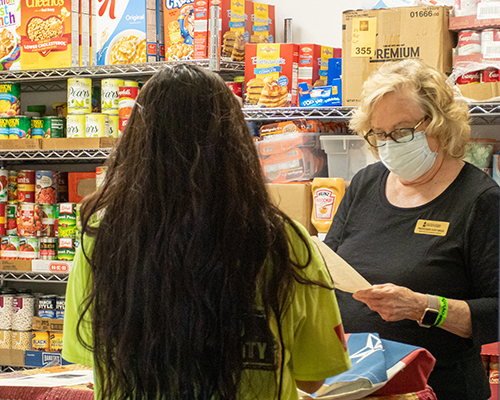 Young student speaking to older woman standing in a food pantry