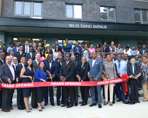 Large crowd with leaders cutting a ribbon outside of a building