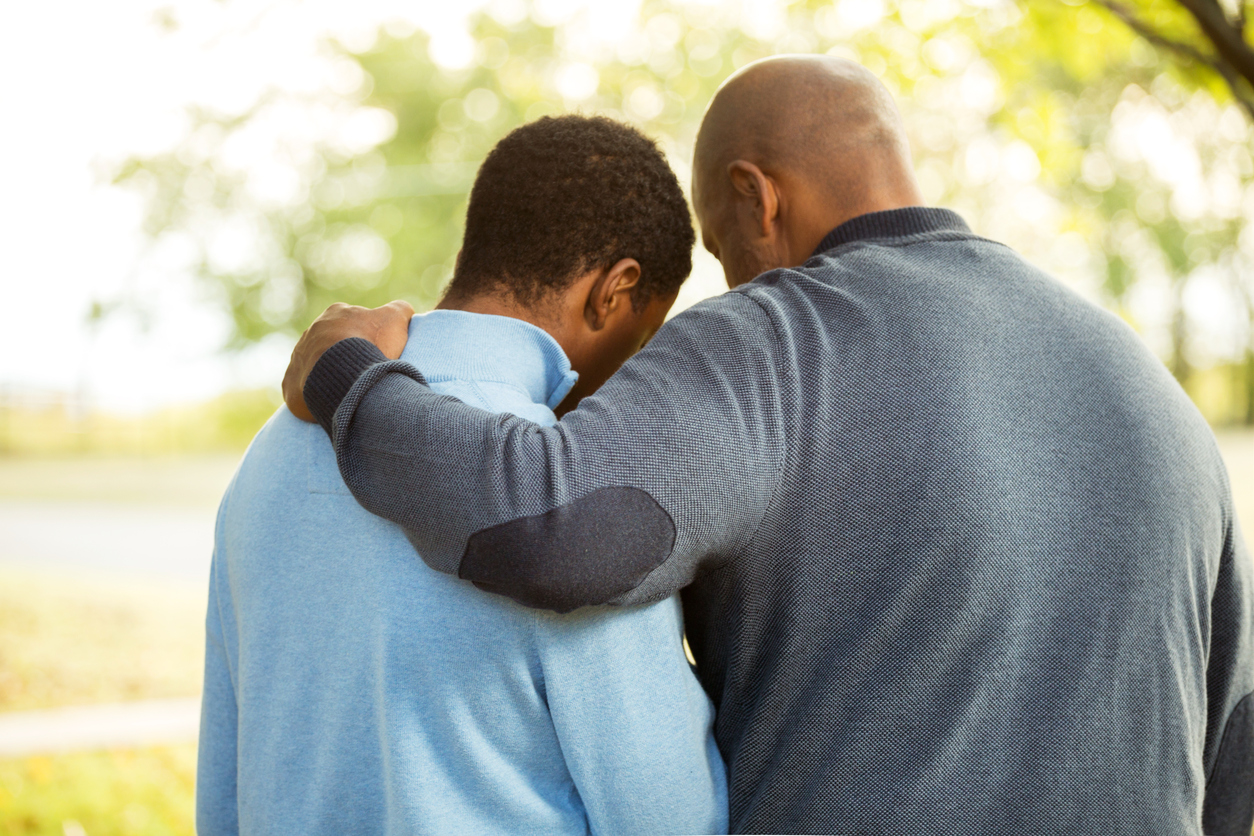 stock photo of father and son in comfort/prayer pose