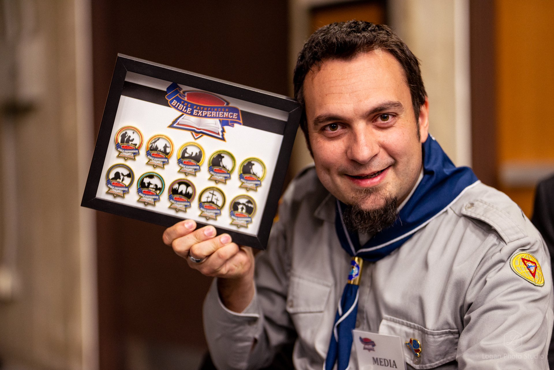 Youth director of the British Union Conference, Dejan Stojkovic, poses with pins from previous PBE events.