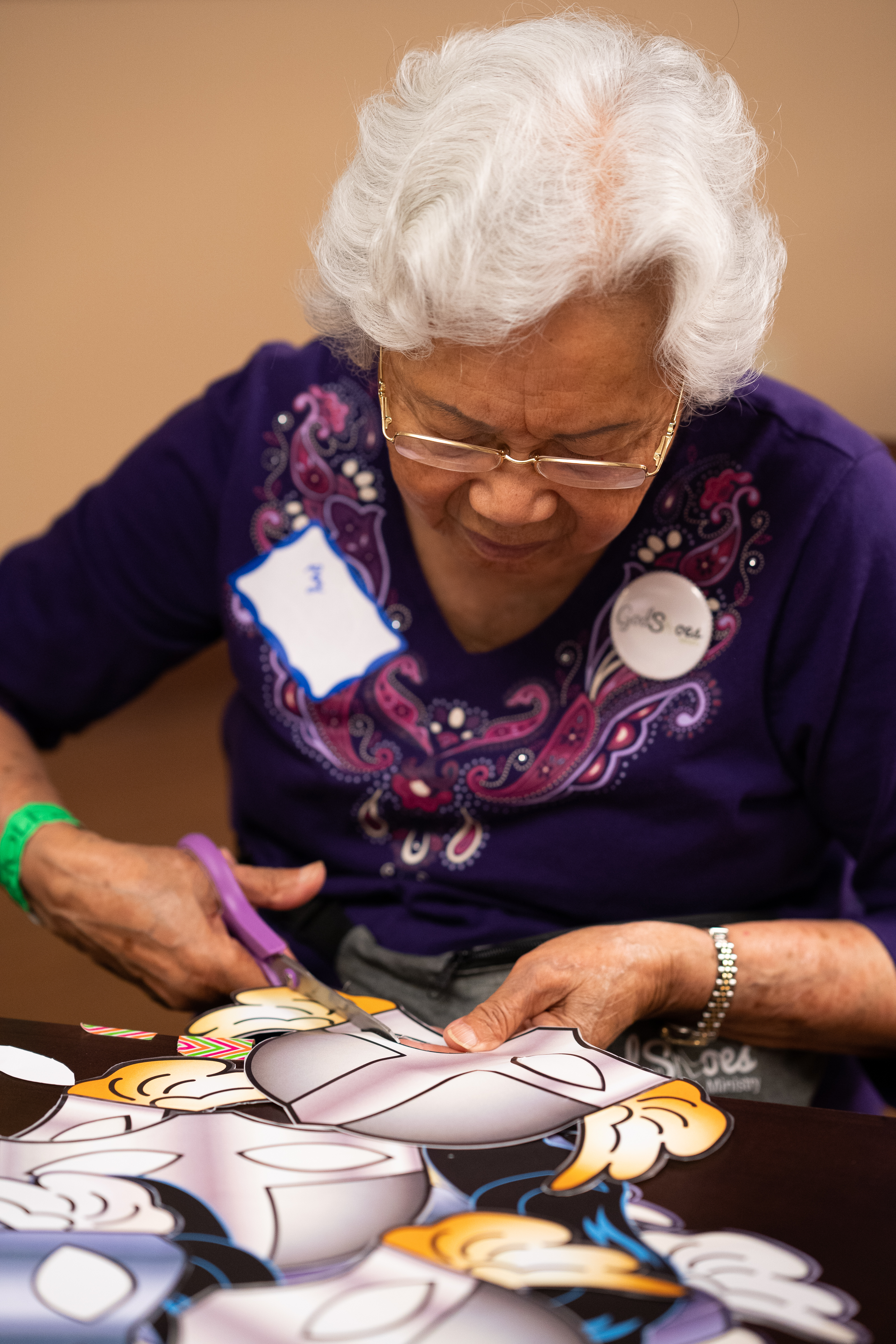 A 97-year-old volunteer cuts out photo-booth props at the New Hope for Kids center.