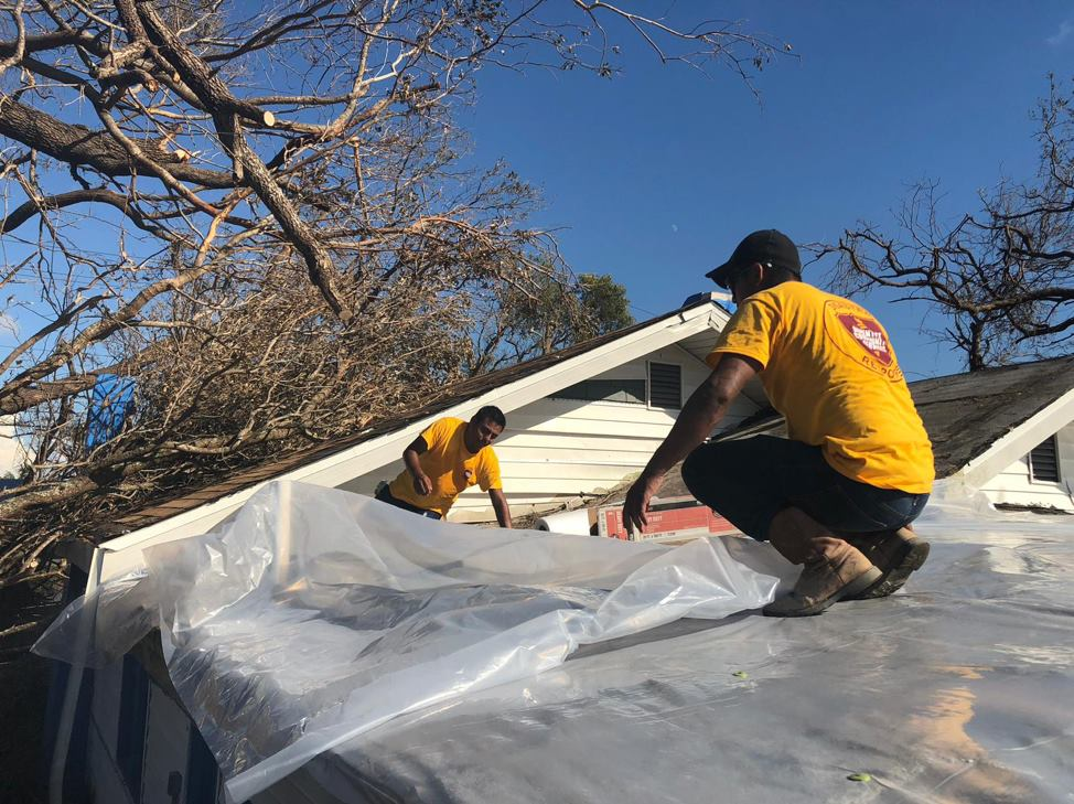 ACS volunteers lay a tarp over an exposed home.