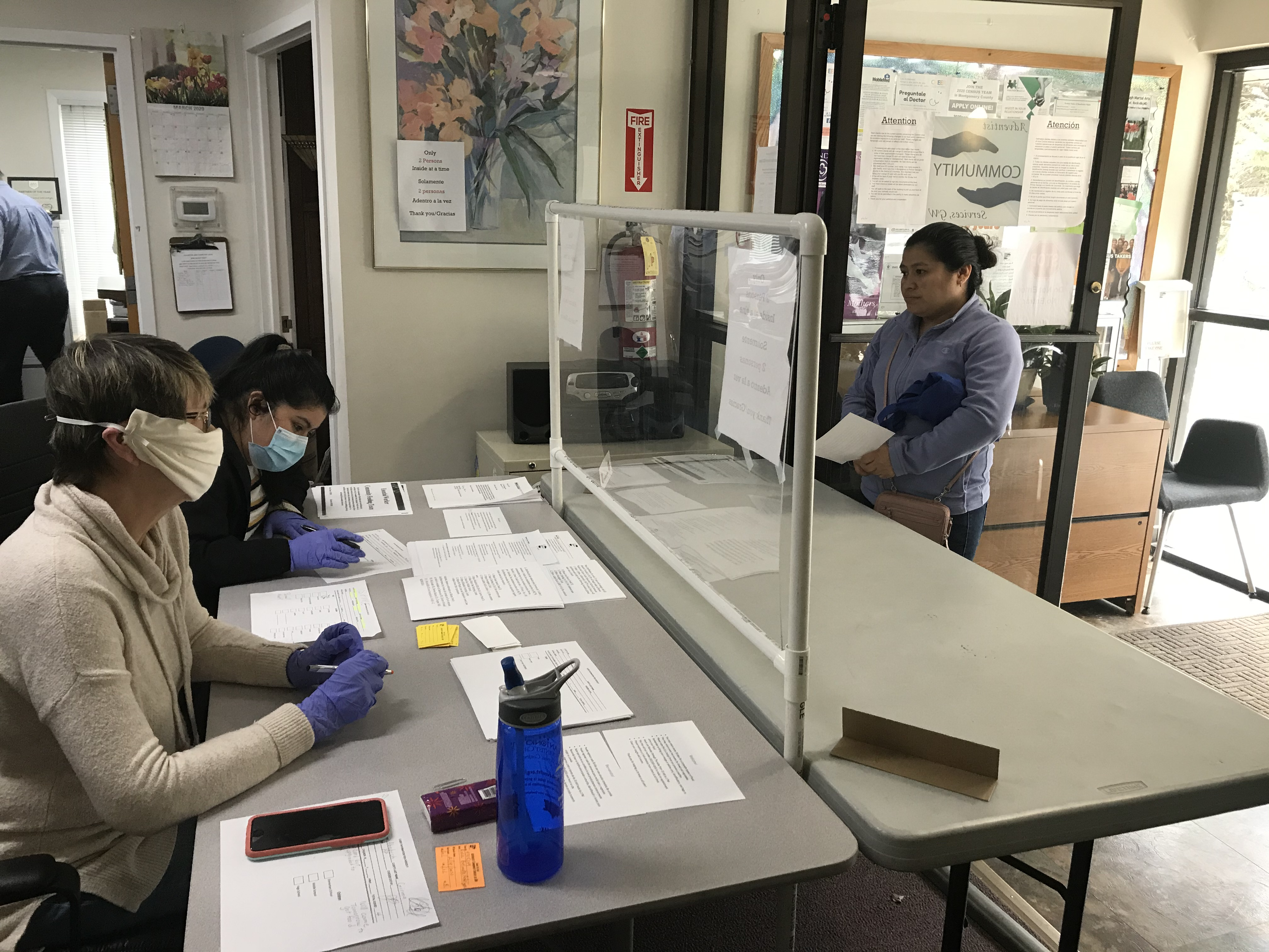 A client of Adventist Community Services Greater Washington checks in before collecting a food basket. Volunteers of ACSGW wear gloves and masks to help in an effort to do all they can to stop the spread of the coronavirus disease.
