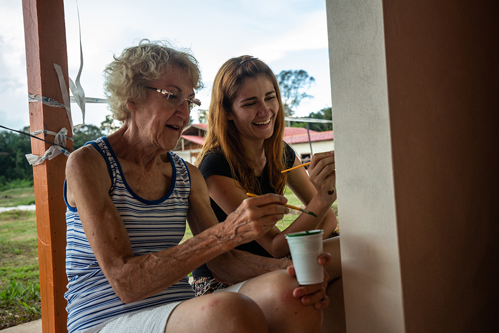 Elaine Halenz (L), retired missionary from the U.S., paints alongside Pollyani Mamedes (R), an art student from Brazil.