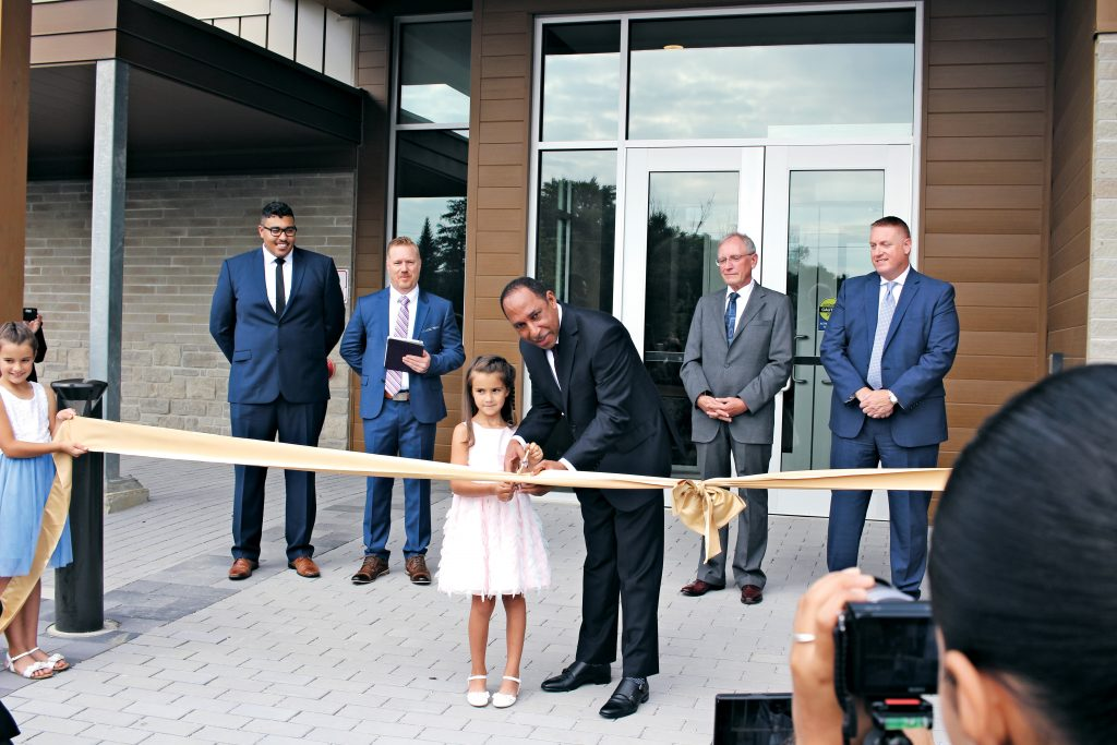 Mansfield Edwards and Eden M. cutting the ribbon, as Really Living youth pastor Benton Lowe; lead pastor, Francis Douville; SDACC president, Mark Johnson; and guest speaker, Dan Linrud look on.