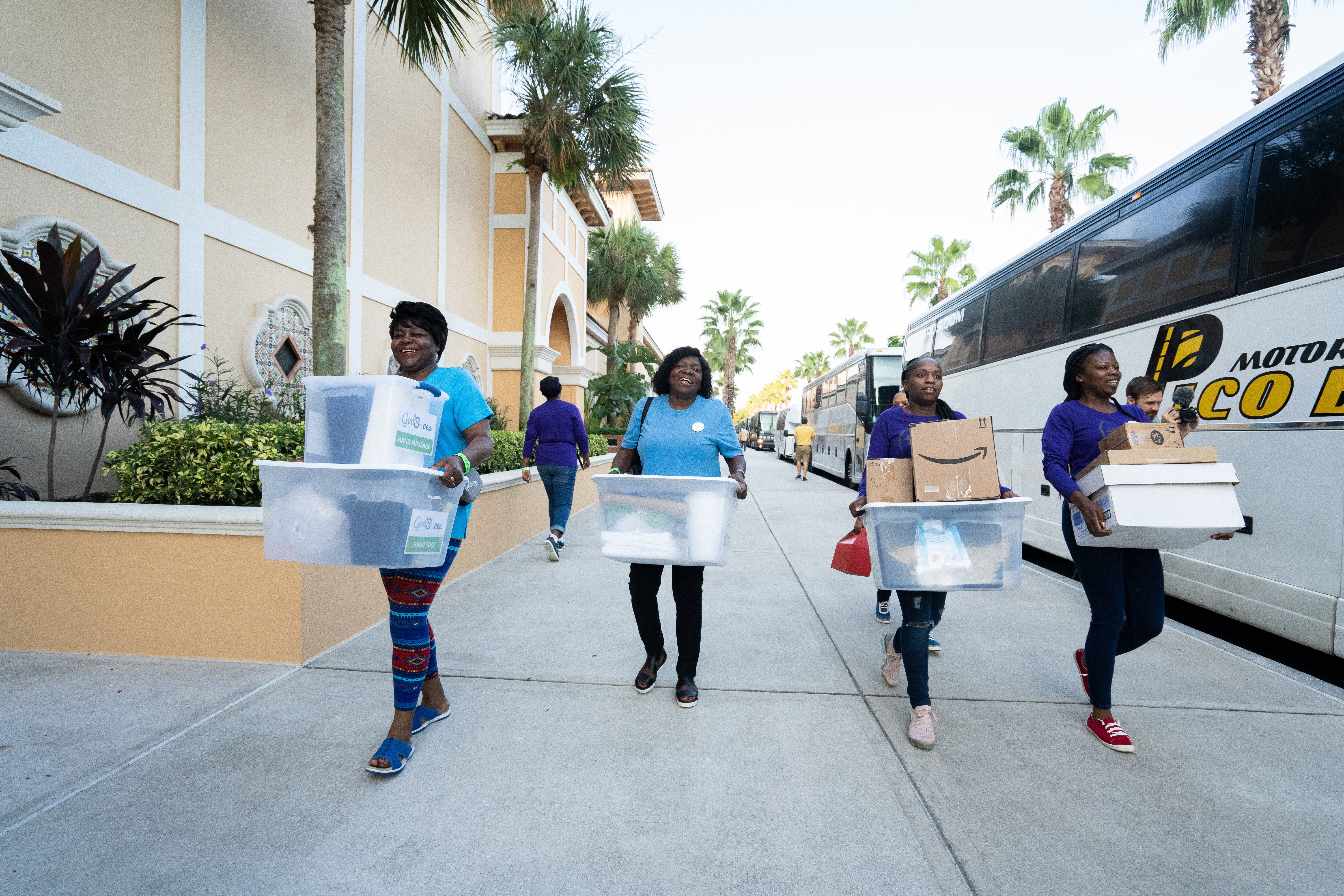 Four women carry supplies to be loaded onto a bus and donated during God in Shoes community service day.