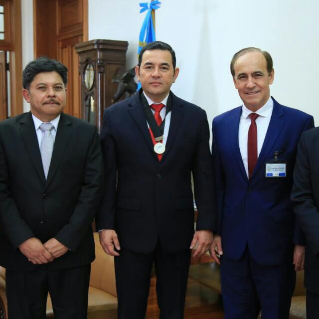 Guatemalan President Jimmy Morales, center, poses for a photo with Pastor Robert Costa, right, and his butler, left. During his March 13 visit, Pastor Costa gave President Morales an Ambassador of Peace medal.