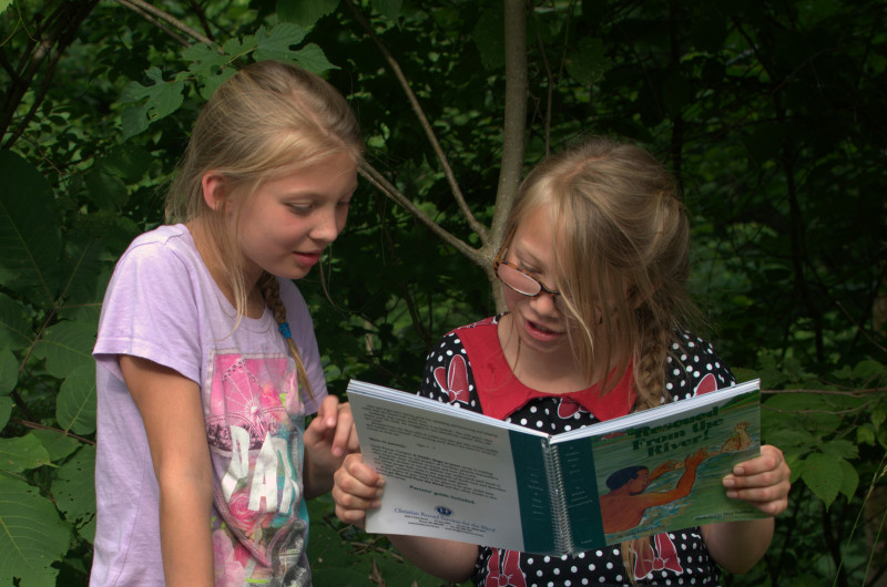 girl reads Braille to her sighted sister