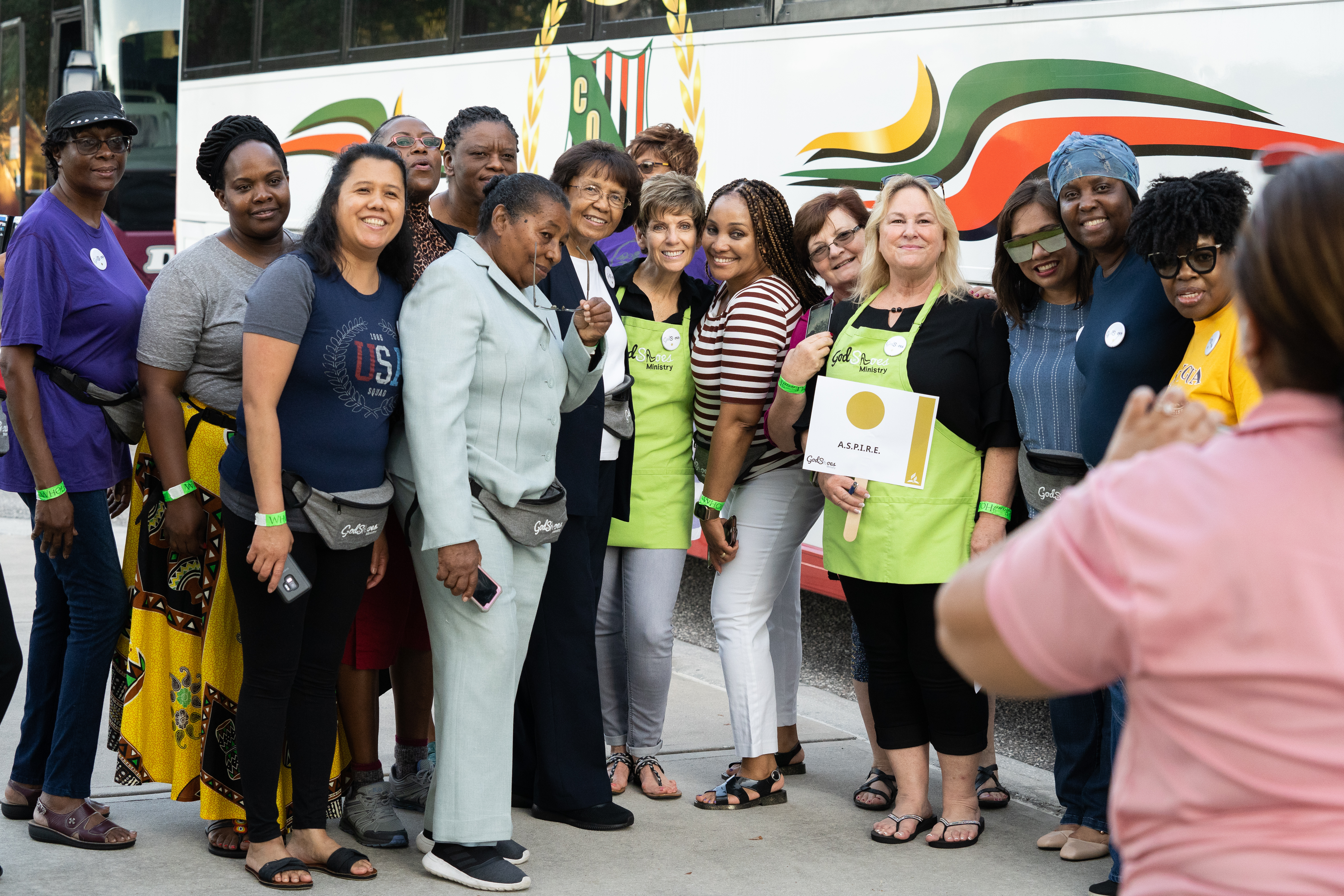 Jo Dubs (center), founder and director of God in Shoes, poses with a group of volunteers preparing to leave the convention center for their service assignment.