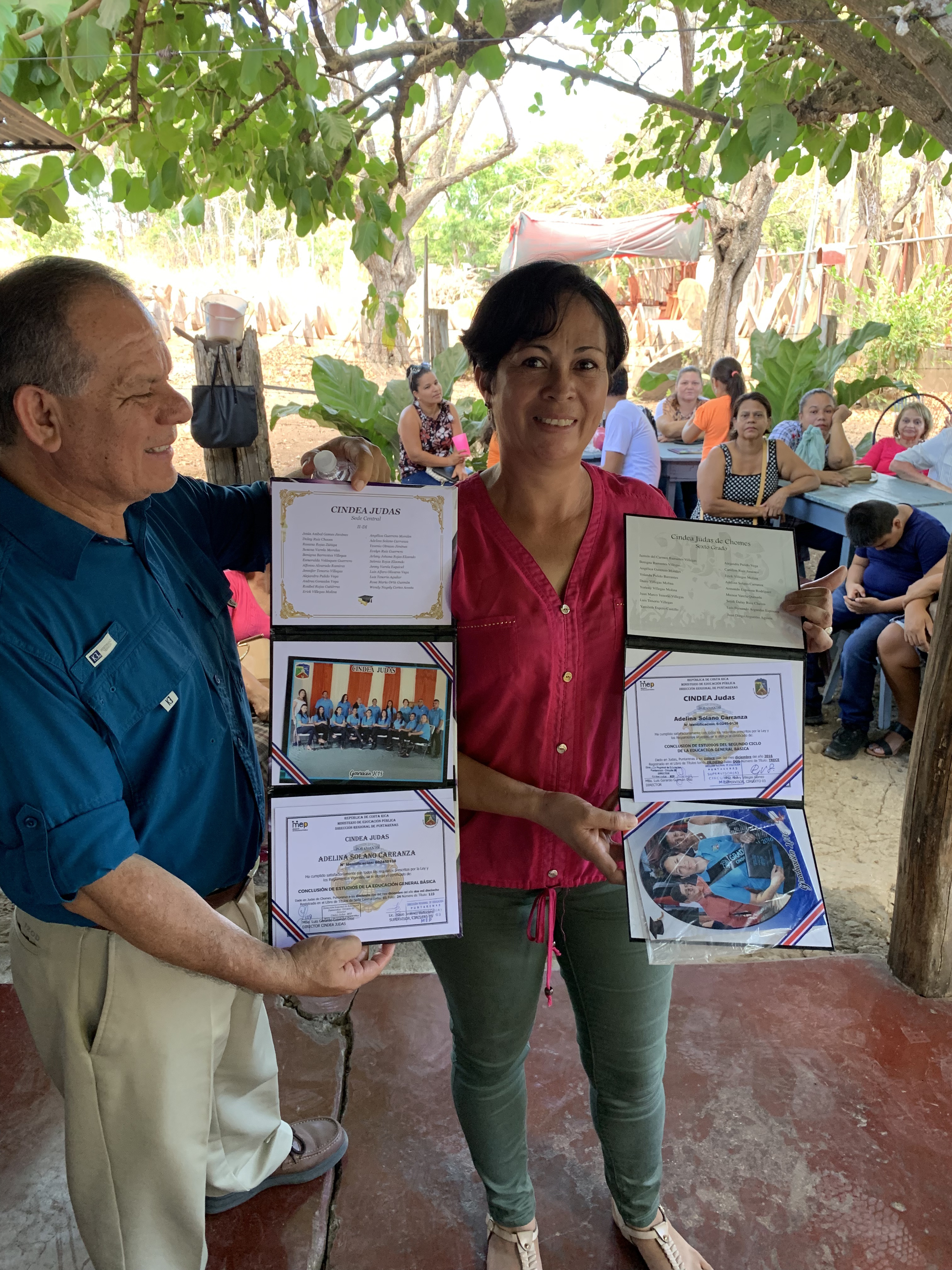 In March 2019, Partners in Mission held an alumni reunion for those who completed the program successfully. This woman (right), with the help of David Poloche, ADRA director for the IAD, shows her elementary and secondary school degrees she earned after completing the Partners in Mission program.