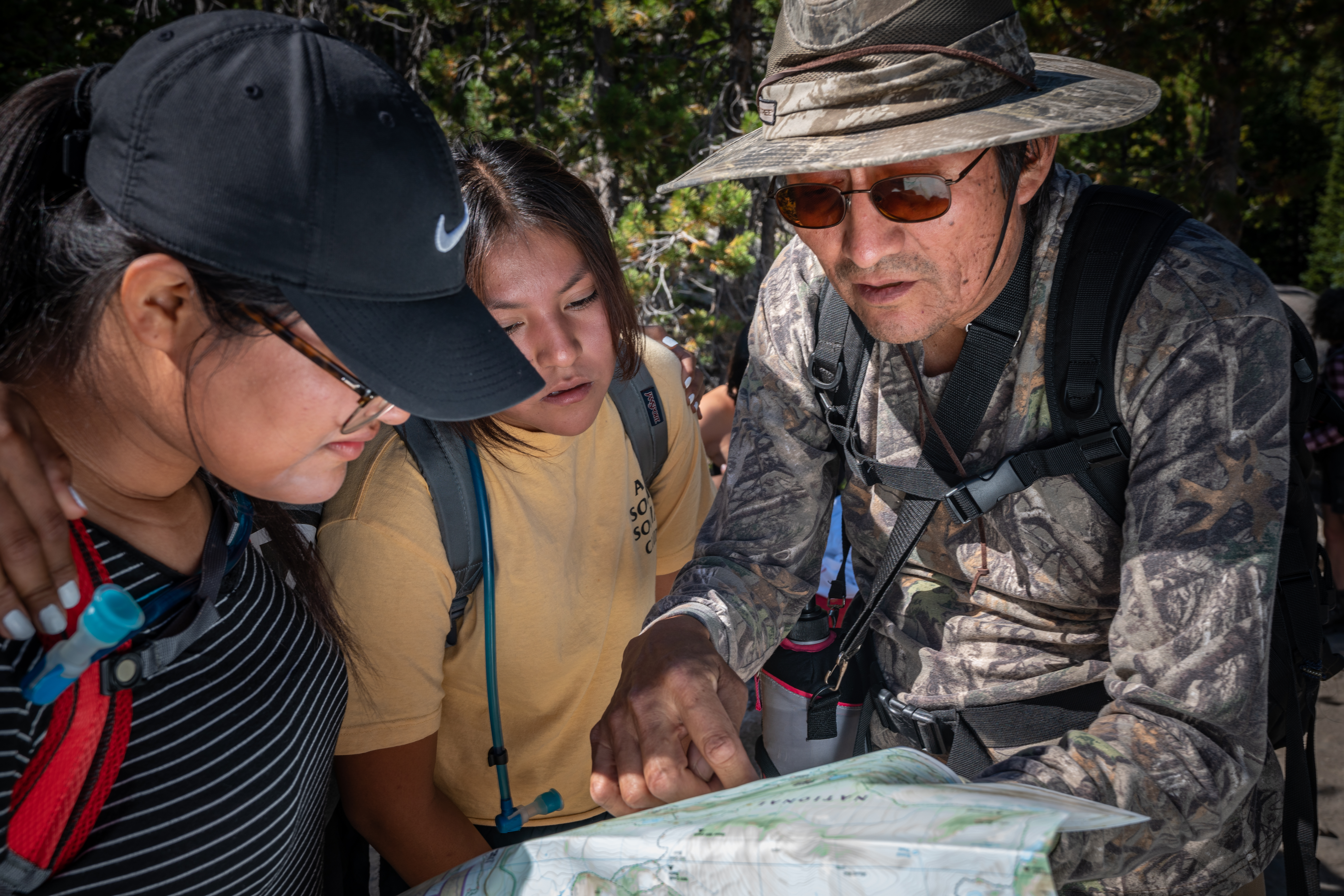 "A teacher of Holbrook Indian School assists students with map reading as part of Holbrook's ""Outdoor School."""