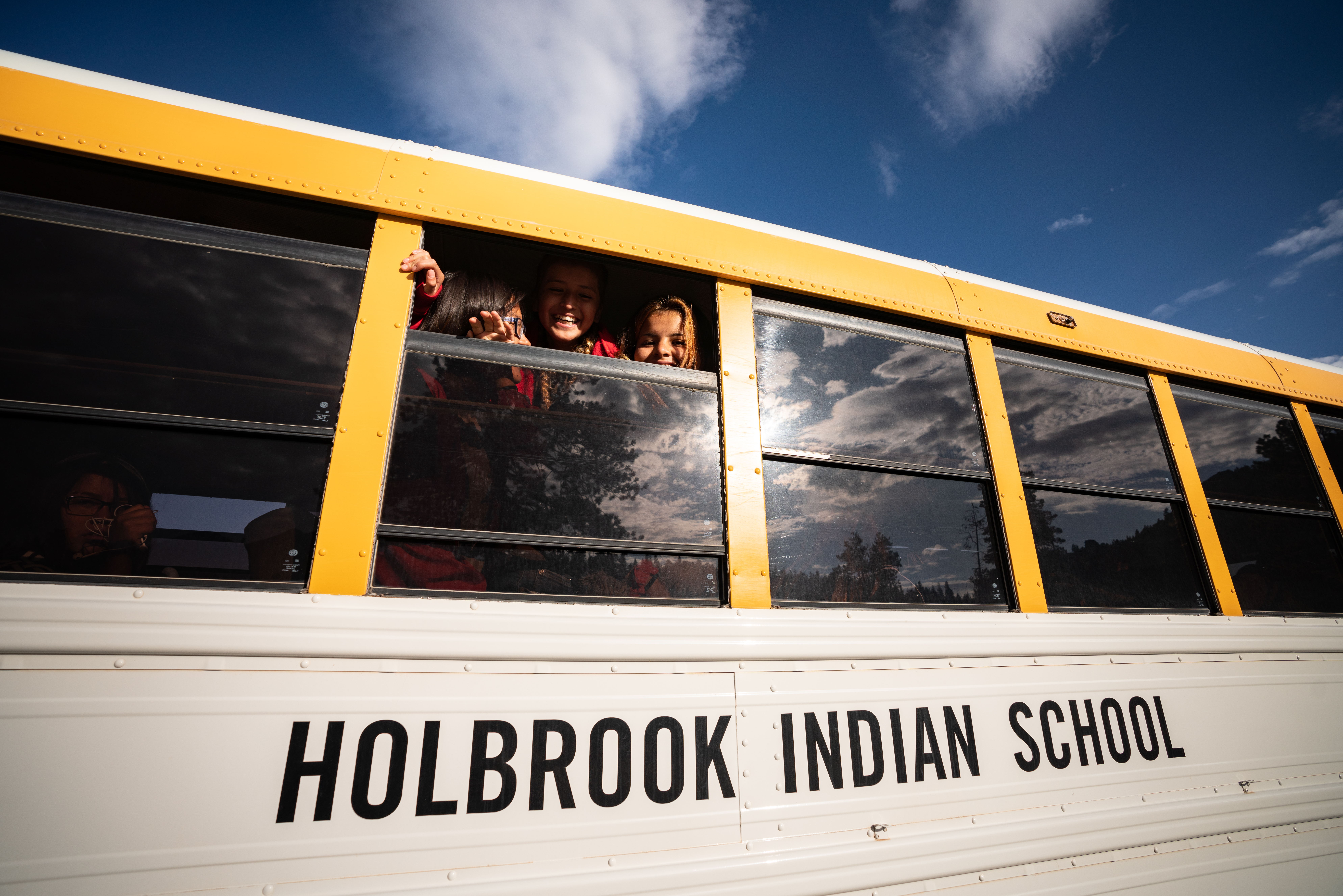 Students of Holbrook Indian School smile from the window of a school bus.