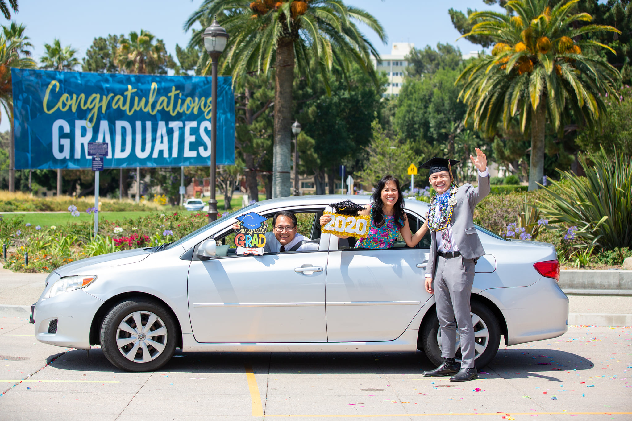 Pastor Vinh Nguyen, Cynthia Nguyen and their son and La Sierra graduate Timothy Nguyen stop near the central fountain at the top of Yaeger Drive for their portrait during La Sierra University's Drive Through Celebration.
