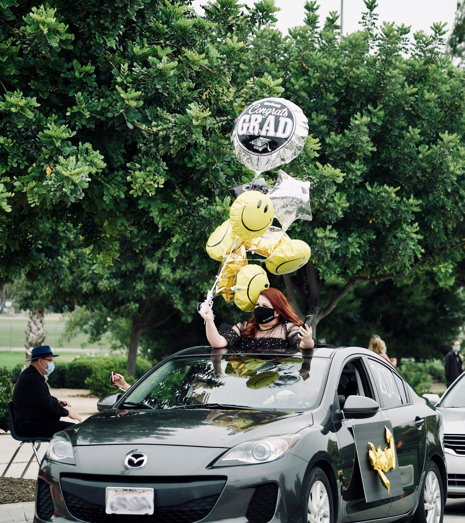 A La Sierra University graduate holds balloons out of a car's sunroof during the