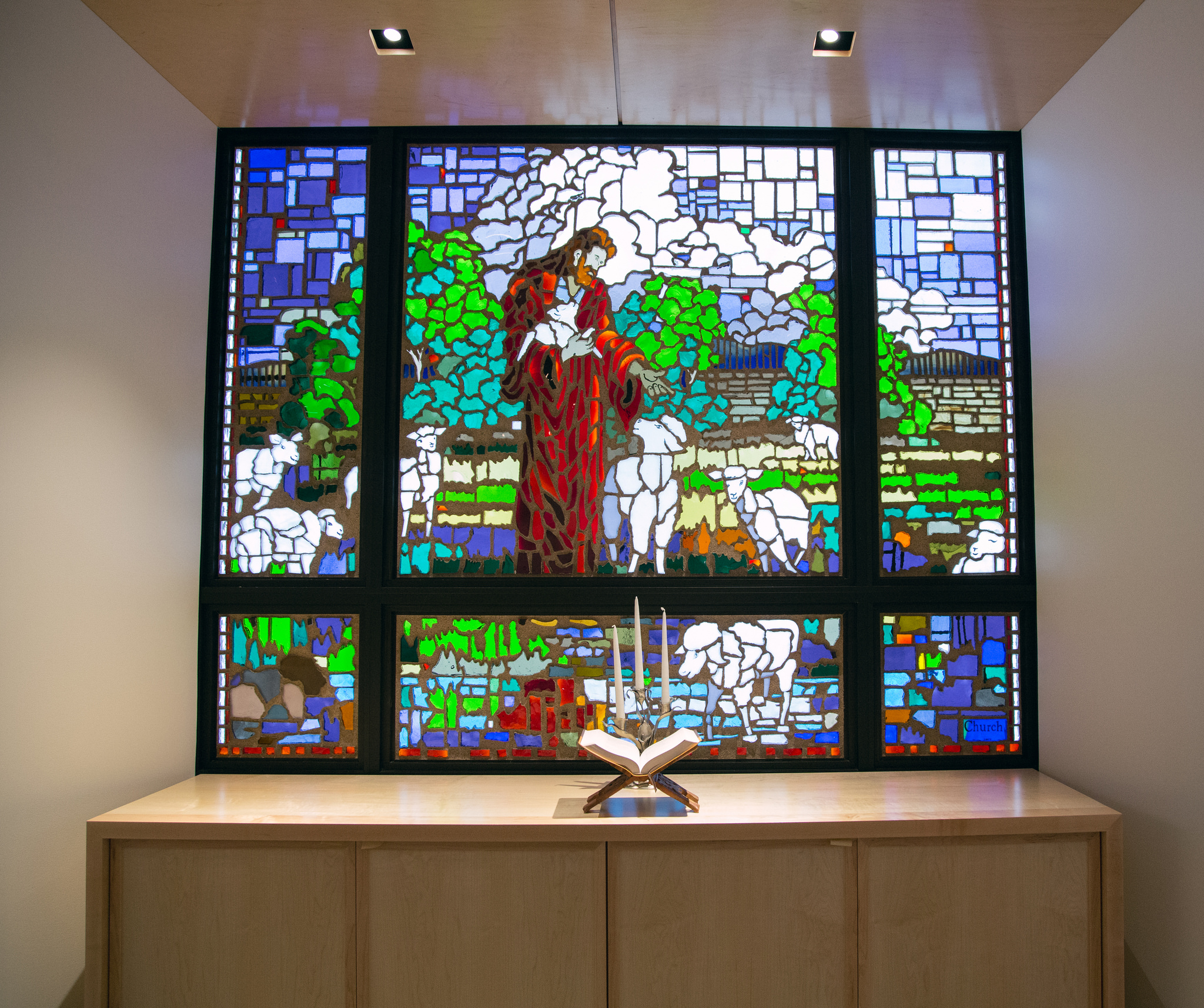 The stained-glassed was created by Clayton Connolly. The glass portrays Jesus as the good shepherd. Jesus is surrounded by nine sheep, representing the division's nine union.