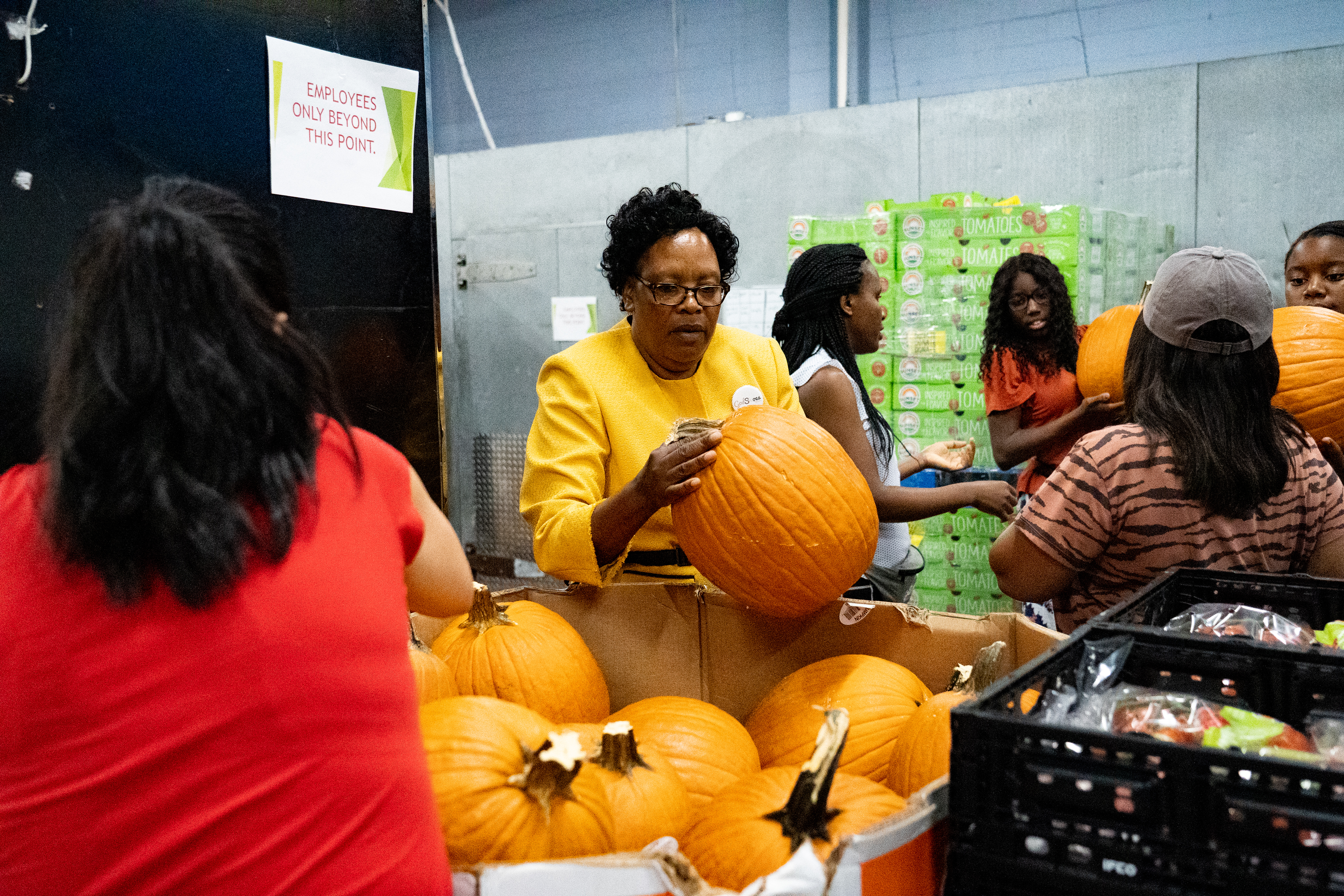 Volunteers organize pumpkins for the United Against Poverty grocery center
