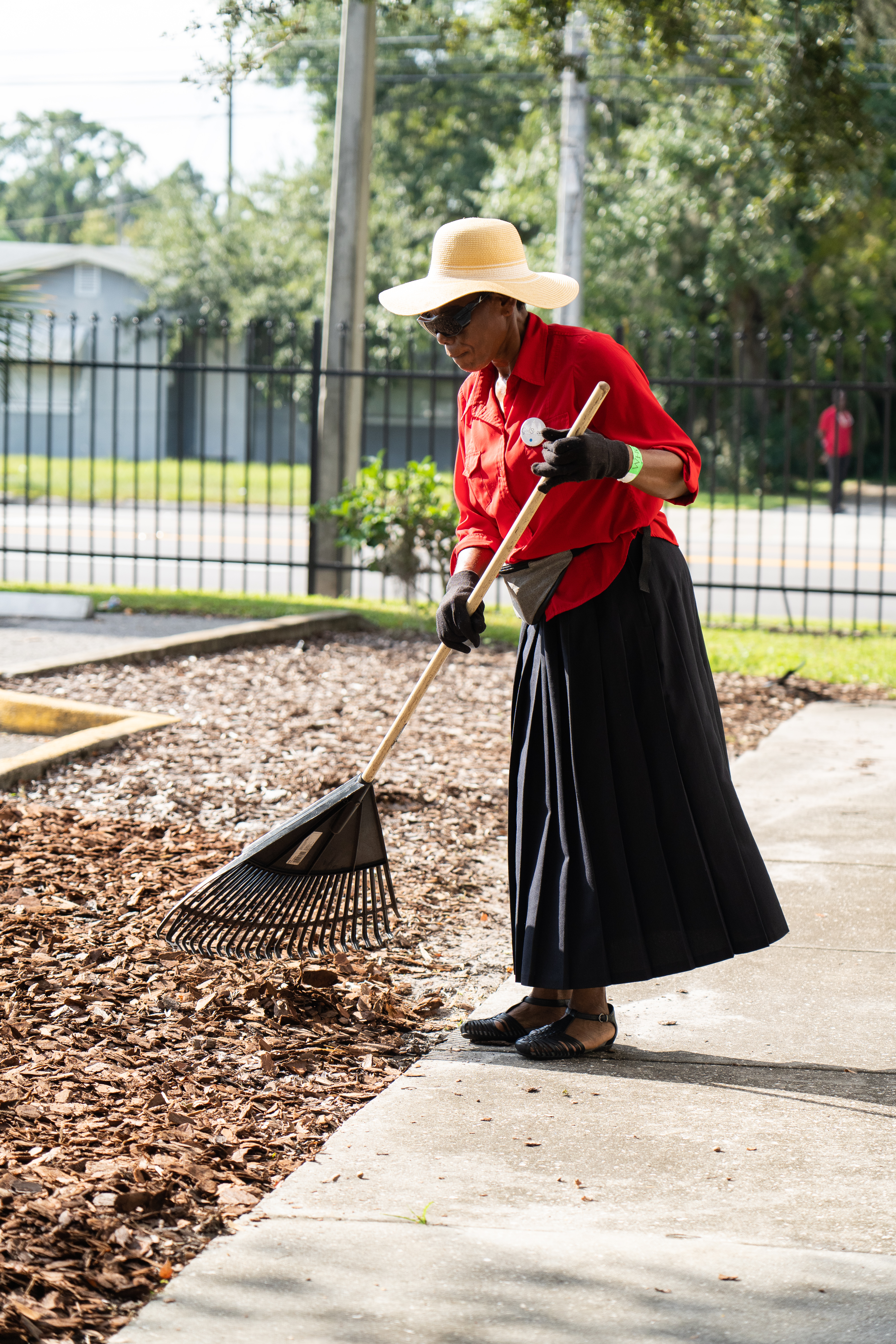 Volunteer arranges mulch on the grounds of the Orlando Union Rescue Mission.
