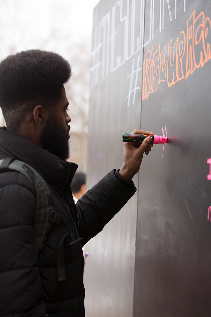 Attendees at the Solidarity Wall, erected outside of the Campus Center for people to write messages of empowerment and support, photo credit Jessica Condon