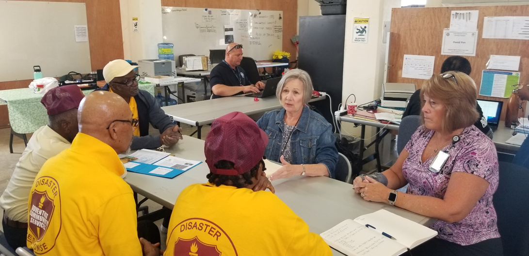 Representatives of the Federal Emergency Management Agency speak with volunteers of Adventist Community Services.