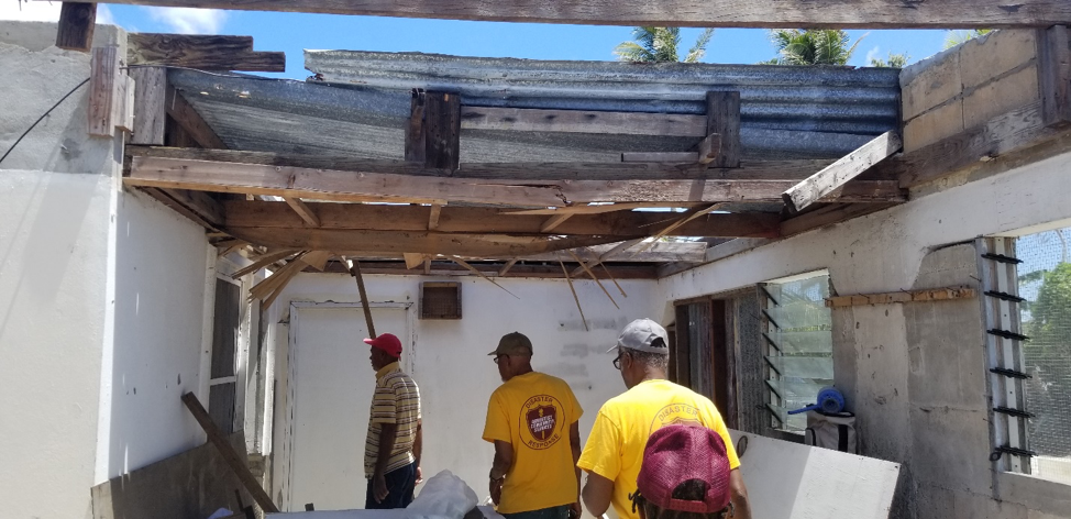 ACS volunteers walk through a damaged building in Saipan.
