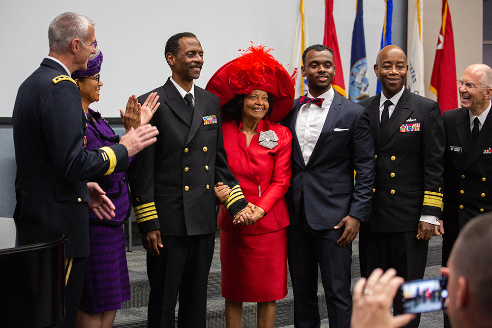 Washington Johnson, II poses with family and colleagues after receiving his new service dress coat, which reflects his new ranking