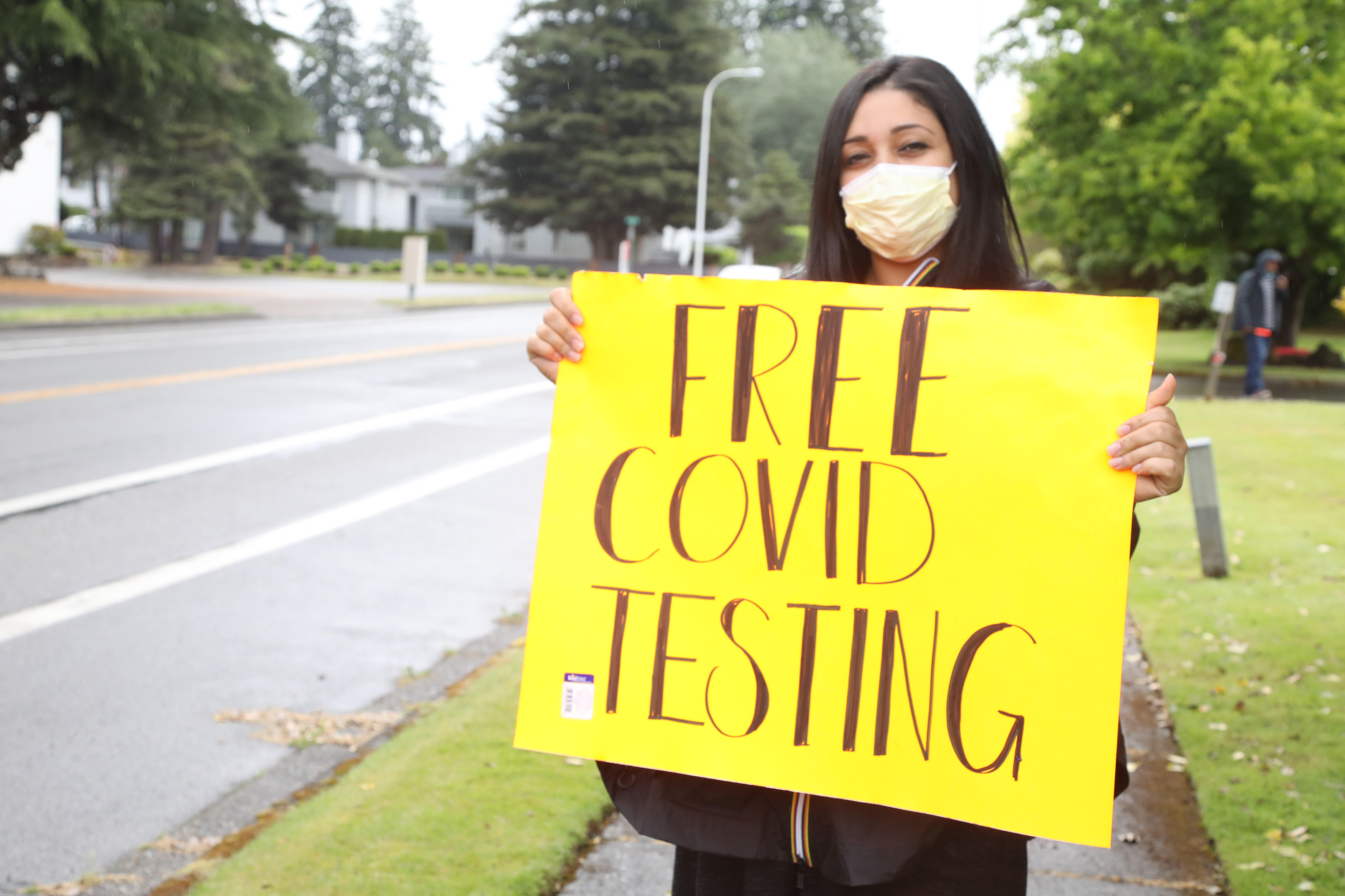 Jackie Langi holds a sign informing drivers about free COVID-19 testing and food boxes.