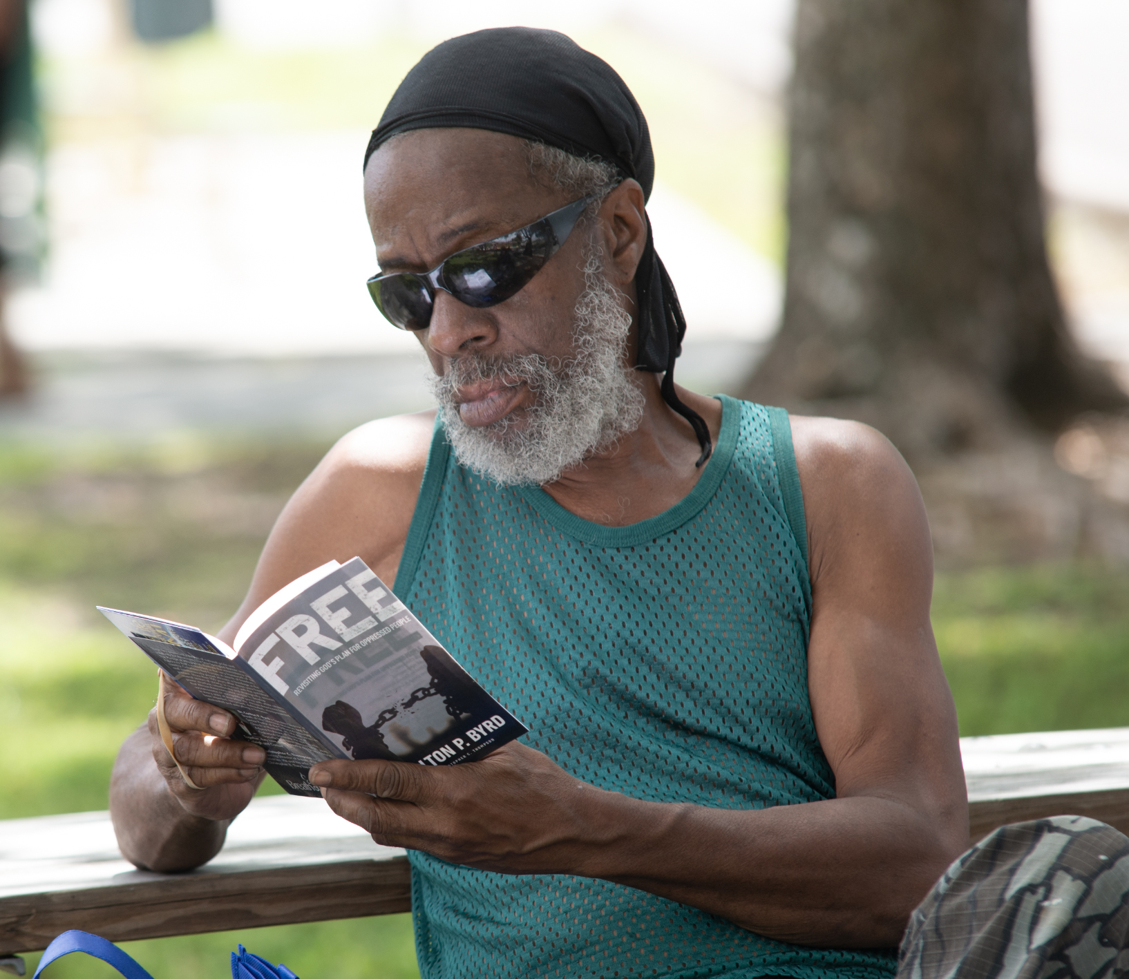 Community member in Miami-area reads a copy of FREE: Revisiting God's Plan for Oppressed People, which was distributed by local church members.