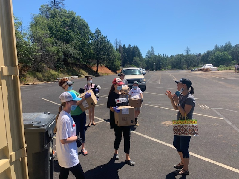 A delivery team gets their instructions as cars line up to receive boxes of fresh produce by Joelle Chinnock. In one day, 5,760 lbs. were distributed one 20 lb. box at a time for each family.