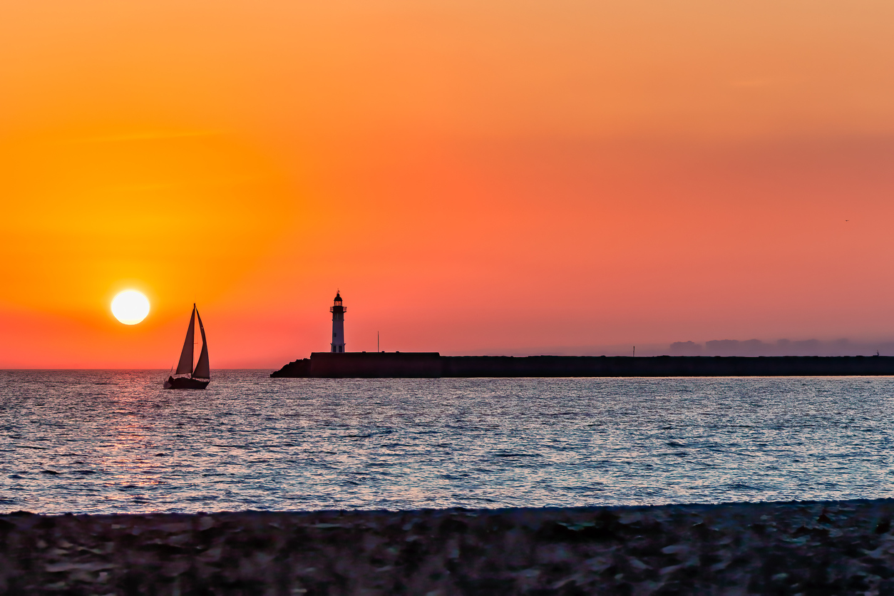 stock photo of sailboat sunset and lighthouse