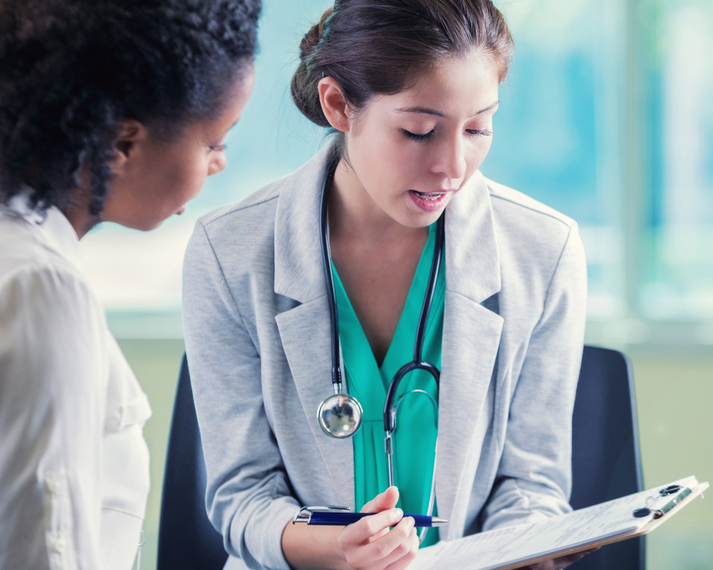 stock photo of female doctor helping patient with chart