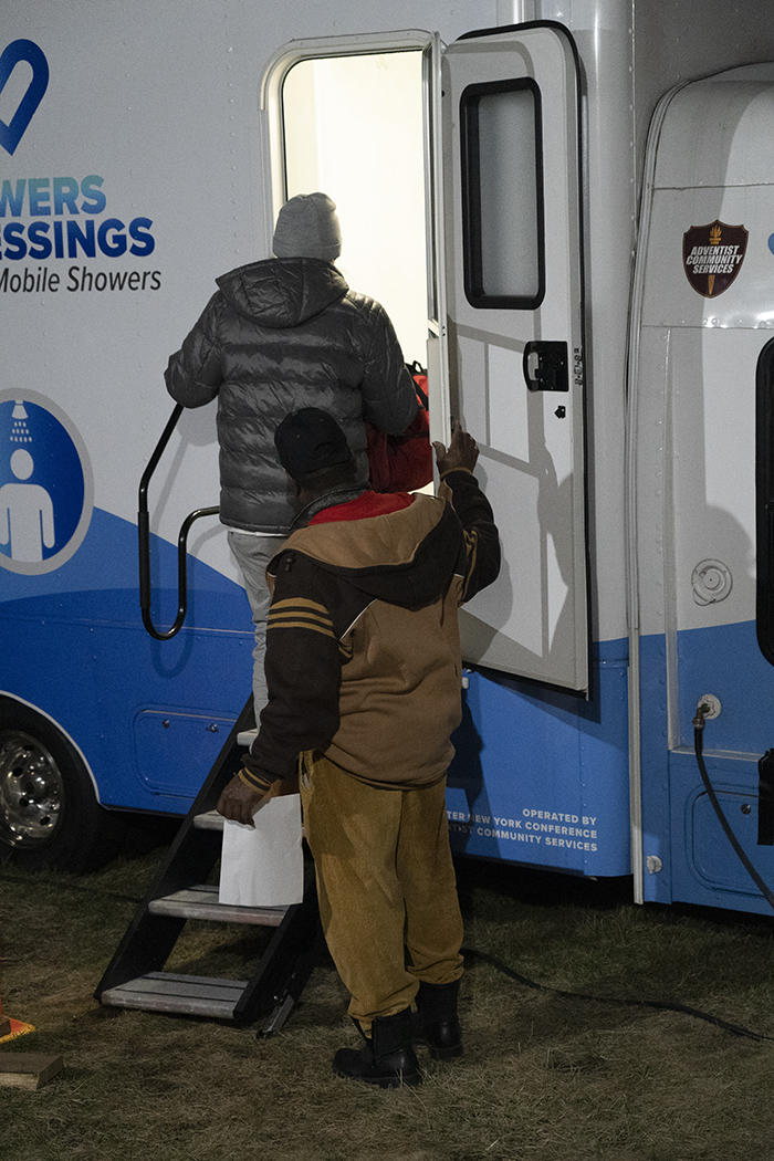 """A client of the Omega Seventh-day Adventist Church's warming center enters the """"Showers of Blessing"""" mobile shower van that's provided by Adventist Community Services Greater New York Conference."""